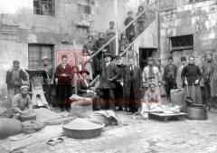 Dans la cour intérieure de l'orphelinat d'Alep: Nora Altounian assise sur un sac de céréales; à sa droite, le pasteur Aharon Chiradjian, probablement en 1919 (coll.Bibliothèque Nubar).