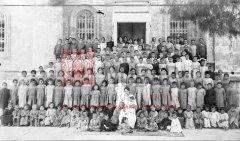 Orphelins recueillis à Jérusalem et ses environs et regroupés dans le monastère arménien des Saints-Jacques, à Jérusalem, en 1918. Au centre, Victoria Archarouni, la directrice de cet orphelinat qui a été transféré à Port-Saïd (coll. Bibliothèque Nubar).